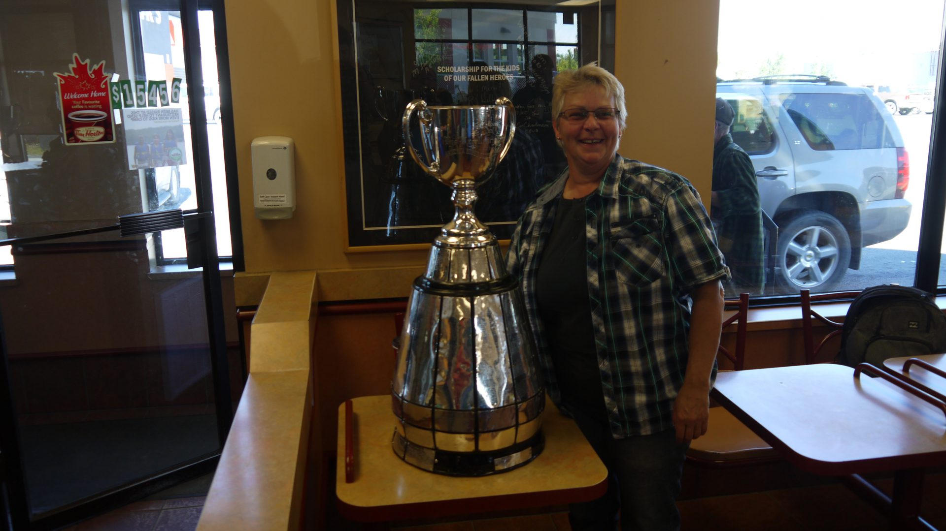 A fan poses with the Grey Cup at Tim Hortons.