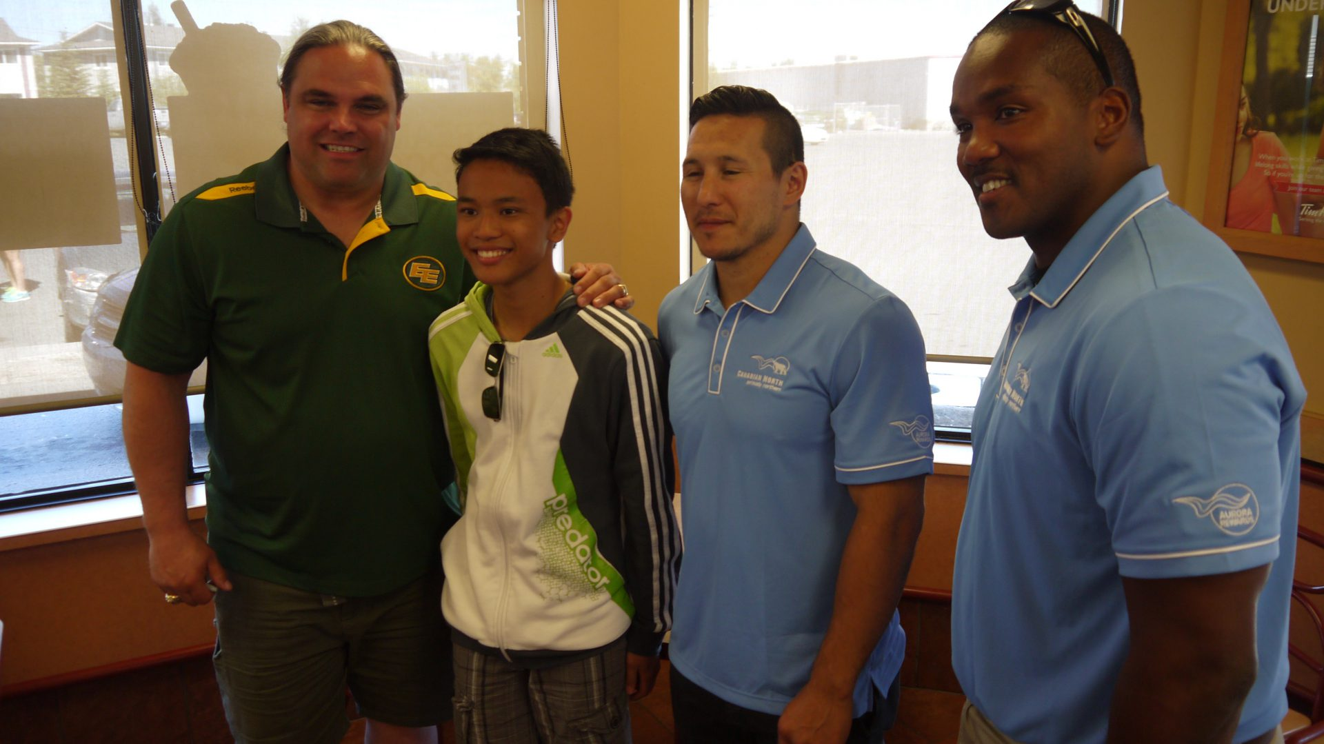 Jed Roberts, Rob Brown and Jordin Tootoo pose with a fan.