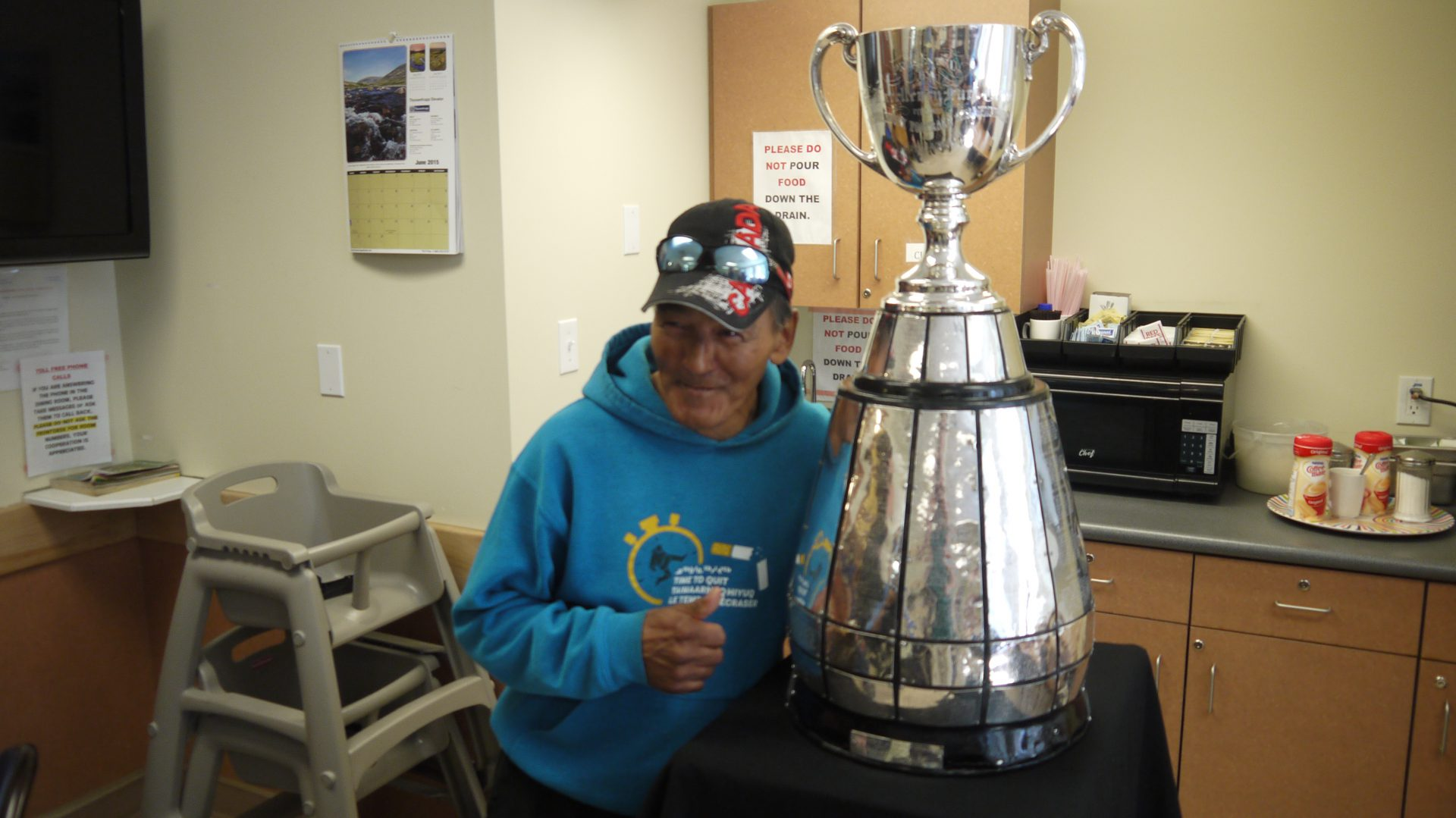 A fan poses with the Grey Cup at Larga Kitikmeot.