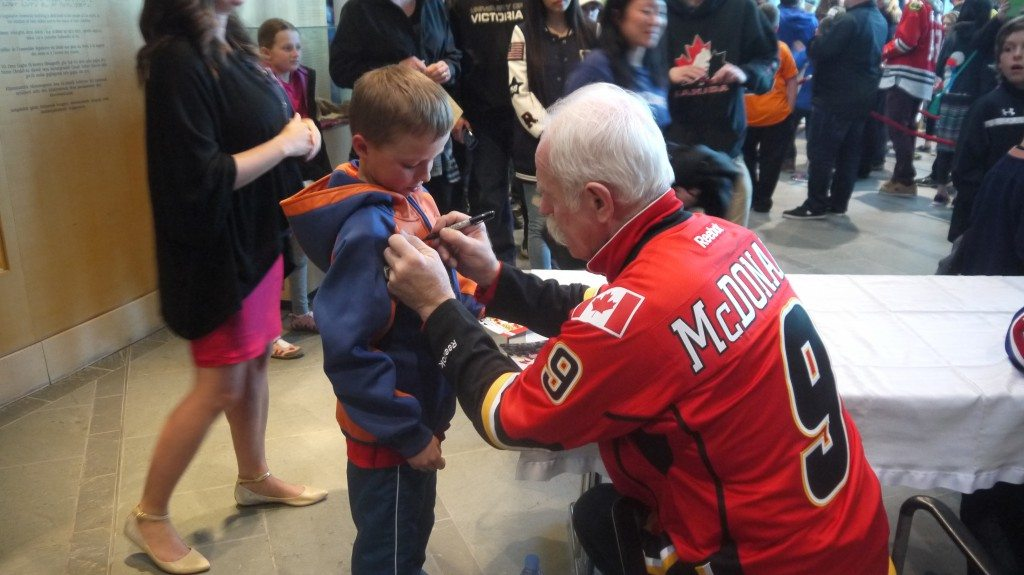 Lanny McDonald signing a young fans' Oilers sweater