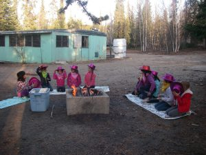 Girl guides sit around a campfire outside the cabin in 2012.