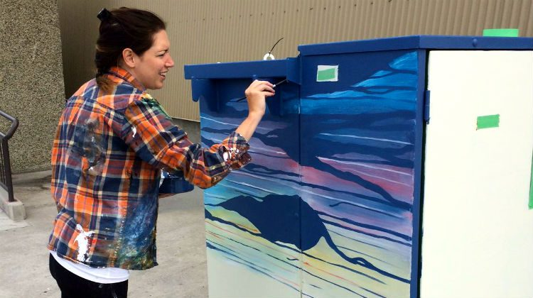 Sarah Bradfield painting a box in front of the Northern United Place.