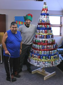 Terry Kuliktana, left, and Daron Letts stand beside the seven-foot tall Christmas tree. The tree is made out of 259 recycled pop cans.