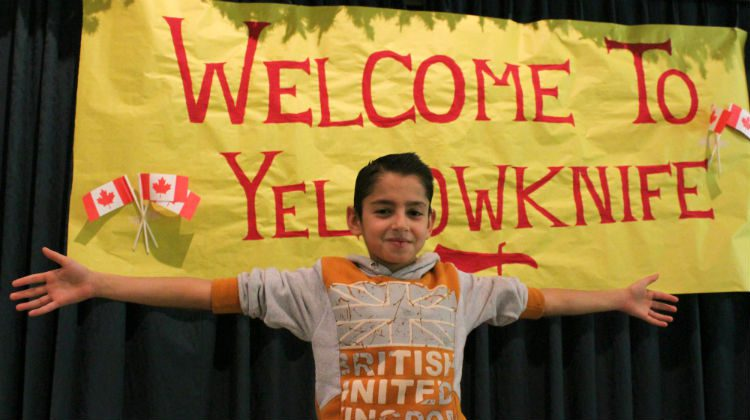 """Muhammad Alhajy stands in front of a """"Welcome to Yellowknife"""" banner at Northern United Place."""